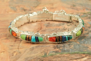 Stunning Bracelet featuring Genuine Turquoise, Gaspeite, Blue Lapis, Spiny Oyster Shell and Black Jade inlaid in Sterling Silver with Fire and Ice Lab Opal Accents. Finished with a Beautiful Sterling Silver Design. The bracelet is Designed by Navajo Artist Calvin Begay. Signed by the artist.