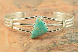 Genuine Number 8 Turquoise set in Sterling Silver Bracelet. The Number 8 mine is located in Eureka County Nevada. Since 1976 there has been no Number 8 Turquoise mined. There is however, an existing stock pile that Mr. Dowell Ward, the last owner of the Number 8 mine, had stocked away for later sorting. The Turquoise is a collector's item--because once the reserve is gone there will be no more material released onto the market. The Gold Mining Company owns the claim to the Number 8 mine and it has been swallowed up by the gold mining operations. This is some of the last Number 8 Turquoise to be had and will be a great addition to your collection. Created by Navajo Artist Phillip Sanchez. Signed by the artist.