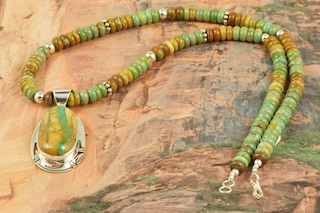Stunning Pendant and Necklace Set featuring Genuine Boulder Turquoise set in Sterling Silver Pendant. Necklace features Genuine Turquoise with Sterling Silver Beads and Clasp. The cabachon is Boulder Turquoise,you can see the veins of Turquoise running through the host rock. The Boulder Turquoise Mine is located in northeast Nevada. It was discovered in 1970 by a Shoshone sheep herder. Production is small due to the remote location and winter weather. Boulder Turquoise is valued for both it's beauty and rarity. Every stone is unique. Created by Navajo Artist Phillip Sanchez. Signed by the artist.