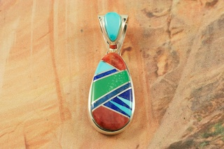 "Beautiful Pendant featuring Genuine Turquoise, Spiny Oyster Shell, Gaspeite and Blue Lapis inlaid between ribbons of Sterling Silver. Accented with Fire and Ice Lab Opals. Free 18"" Sterling Silver Chain with Purchase of Pendant. Designed by Navajo Artist Calvin Begay. Signed by the artist."