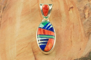 "Beautiful Pendant featuring Genuine Turquoise, Spiny Oyster Shell and Blue Lapis inlaid in Sterling Silver. Fire and Ice Lab Opal Accents. Free 18"" Sterling Silver Chain with Purchase of Pendant. Designed by Navajo Artist Calvin Begay. Signed by the artist."