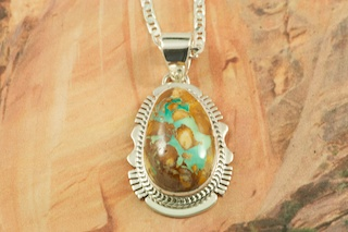 "Mother Nature is Amazing! The beautiful pattern in the stone (called the matrix) is all natural. Genuine Boulder Turquoise set in Sterling Silver Pendant. Free 18"" Sterling Silver Chain with purchase. Created by Navajo Artist John Nelson. Signed by the artist. The cabachon is Boulder Turquoise,you can see the veins of Turquoise running through the host rock. The Boulder Turquoise Mine is located in northeast Nevada. It was discovered in 1970 by a Shoshone sheep herder. Production is small due to the remote location and winter weather. Boulder Turquoise is valued for both it's beauty and rarity. Every stone is unique."
