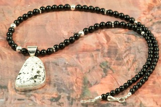 Genuine White Buffalo Turquoise set in Sterling Silver Pendant on a Genuine Black Onyx Necklace with Sterling Silver Beads and Clasp. This Beautiful Stone is formed from the minerals Calcite and Iron. It is mined near Tonopah Nevada. Created by Navajo Artist Eva King. Signed by the artist.