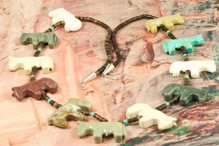 Beautiful Hand Carved Horse Fetish Necklace featuring Genuine Gemstones accented with Pen Shell Heishi. Finished with Sterling Silver Cones and Clasp. Created by Zuni Artist Corrine Ramirez. Corrine uses Genuine Turquoise, White Marble, Serpentine, Picture Marble and Pipestone in her fetish necklaces. The placement and assortment of stones in each necklace varies.