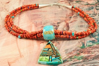Beautiful Pendant inlaid with Genuine Turquoise, Spiny Oyster Shell and Jet. The 4 Strand Necklace features Genuine Coral with accents of Genuine Turquoise and Jet with Sterling Silver Cones and Clasp. Created by Santo Domingo Artist Chris Nieto. Signed by the Artist. The Santo Domingo Pueblo is in New Mexico, near Santa Fe.