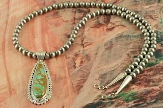 Stunning Pendant and Necklace Set. Genuine Manassa Turquoise set in Sterling Silver Pendant. Sterling Silver Navajo Pearls Necklace with Sterling Silver Beads and Clasp. Created by Navajo Artist Joe Piaso. Signed by the artist. This Turquoise is also referred to as King's Manassa Turquoise. The Manassa Turquoise mine is located in Manassa, Conejos County, Colorado.