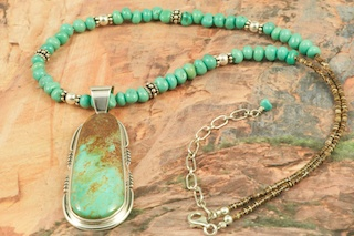 Stunning Pendant and Necklace Set featuring Genuine Crow Springs Turquoise set in Sterling Silver Pendant. Necklace features Genuine Turquoise and Pen Shell Heishi with Sterling Silver Beads and Clasp. Created by Navajo Artist Arkie Nelson. Signed by the artist. The Crow Springs Mine is located near Tonopah, Nevada. The Crow Springs Turquoise Mine was closed for many years. It recently was opened by Dennis and Lucy Cordova. The Smith family previously owned the mine. This family had been mining turquoise in Nevada since the 1870�s. In 1909, William Petry discovered a deposit one mile southwest of the Crow Springs claim. In 1939, Ann Cooper Hewitt, heiress to the Cooper Hewitt fortune, made from inventing the mercury-vapor lamp and the first fluorescent lighting, filed claim to the mine and built a home there, which she called AnnJax. She did little work on the property and subsequently abandoned it.