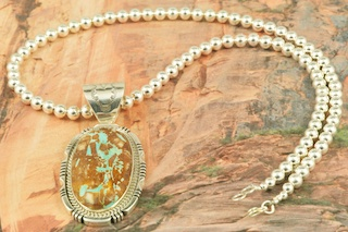 "Stunning Pendant and Necklace Set. Genuine Boulder Turquoise set in Sterling Silver Pendant. 18"" Sterling Silver Bead Necklace is included. Created by Navajo Artist Freddy Charley. Signed by the artist. The cabachon is Boulder Turquoise, you can see the veins of Turquoise running through the host rock. The Boulder Turquoise Mine is located in northeast Nevada. It was discovered in 1970 by a Shoshone sheep herder. Production is small due to the remote location and winter weather. Boulder Turquoise is valued for both it's beauty and rarity. Every stone is unique."