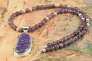 Genuine Charoite set in Sterling Silver Pendant on a Genuine Amethyst Necklace with Sterling Silver Beads and Clasp. Created by Navajo Artist Freddy Charley. Signed by the artist. Charoite is a Beautiful and interesting gemstone first introduced in the US around 1976. It's vivid colors range from lavender to deep chatoyant purple. It is mined in Siberia Russia near Charo River, Lake Baikal region. High grade charoite is distinguished by mixtures of deep rich purple and silky zones, in swirly and/or needle-like chatoyant patterns/sprays.