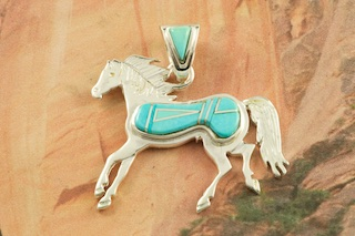 "Genuine Sleeping Beauty Turquoise inlaid between ribbons of Sterling Silver. Free 18"" Sterling Silver Chain with Purchase of Pendant. Horse Pendant Designed by Navajo Artist Calvin Begay. Signed by the artist."