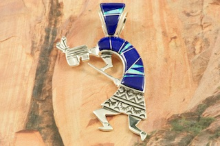 "Beautiful Kokopelli Pendant featuring Genuine Blue Lapis inlaid between ribbons of Sterling Silver. Stunning Fire and Ice Lab Opal Accents. Free 18"" Sterling Silver Chain with purchase of pendant. Designed by Navajo Artist Calvin Begay. Signed by the artist."