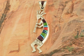 "Stunning Kokopelli Pendant featuring Genuine Turquoise, Spiny Oyster Shell, Blue Lapis and Black Jade inlaid in Sterling Silver. Free 18"" Sterling Silver Chain with purchase of Pendant. Designed by Navajo Artist Calvin Begay. Signed by the artist."