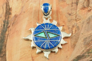 "Stunning Sun Pendant featuring Genuine Denim Lapis and Black Jade inlaid between ribbons of Sterling Silver. Beautiful Fire and Ice Lab Opal Accents. Free 18"" Sterling Silver Chain with Purchase of Pendant. Designed by Navajo Artist Calvin Begay. Signed by the artist."