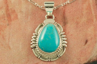 "Genuine Manassa Turquoise set in Sterling Silver Pendant. This Turquoise is also referred to as King's Manassa Turquoise. The Manassa Turquoise mine is located in Manassa, Conejos County, Colorado. Created by Navajo Artist Bennie Ration. Signed. Free 18"" Sterling Silver Chain with purchase of pendant."