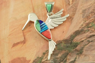 "Beautiful Hummingbird Pendant featuring Genuine Turquoise, Blue Lapis, Magnesite and Spiny Oyster Shell inlaid in Sterling Silver. Free 18"" Sterling Silver Chain with Purchase of Pendant. Designed by Navajo Artist Calvin Begay. Signed by the artist."
