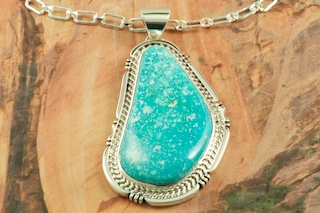 "Genuine High Grade Kingman Turquoise set in Sterling Silver Pendant. Created by Navajo Artist Freddy Charley. Signed by the artist. The Mineral Park Mine, in the Cerbat Mountains 14 miles northwest of Kingman, was first mined by Indians centuries before white man came to the area. It is one of the three sites of prehistoric mining localities in the state of Arizona. Mineral Park was the most extensively worked area by the Indians of the three. S.A. �Chuck� Colbaugh found a cache of stone hammers uncovered in ancient trenches and tunnels, when he had the turquoise mining concession in May of 1962. Ithaca Peak and Turquoise Mine (formally called Aztec Mountain or Aztec Peak) are the most famous of the peaks in the area containing turquoise. Free 18"" Sterling Silver Chain with purchase of pendant."
