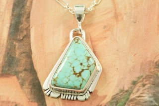 """Genuine Number 8 Mine Turquoise Stone set in Sterling Silver Pendant. Free 18"""" Sterling Silver Chain with Purchase of Pendant. Created by Navajo Artist Phillip Sanchez. Signed by the artist. The Number 8 mine is located in Eureka County Nevada. Since 1976 there has been no Number 8 Turquoise mined. There is however, an existing stock pile that Mr. Dowell Ward, the last owner of the Number 8 mine, had stocked away for later sorting. The Turquoise is a collector's item--because once the reserve is gone there will be no more material released onto the market. The Gold Mining Company owns the claim to the Number 8 mine and it has been swallowed up by the gold mining operations. This is some of the last Number 8 Turquoise to be had and will be a great addition to your collection."""