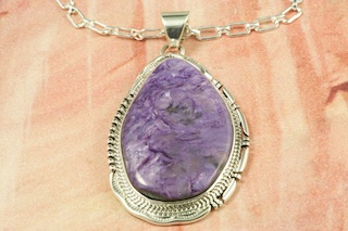 """Genuine Charoite set in Sterling Silver Pendant. Free 18"""" Sterling Silver Chain with Purchase of Pendant. Charoite is a Beautiful and interesting gemstone first introduced in the US around 1976. It's vivid colors range from lavender to deep chatoyant purple. It is mined in Siberia Russia near Charo River, Lake Baikal region. High grade charoite is distinguished by mixtures of deep rich purple and silky zones, in swirly and/or needle-like chatoyant patterns/sprays. Free 18"""" Sterling Silver Chain with Purchase of Pendant. Created by Navajo Artist John Nelson. Signed by the artist."""