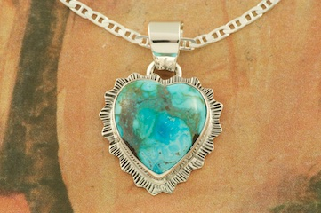 Genuine Candelaria Turquoise set in Sterling Silver Heart Pendant. Created by Navajo Artist Lyle Piaso. Signed by the artist. Free 18 inch Sterling Silver Chain with purchase of pendant. Candelaria Turquoise comes from the large Candelaria Silver and Gold mine in Nevada in an area not to far from Tonopah. It is currently closed with no mining activity and as such Candelaria turquoise is rare and considered a collectable. The turquoise in this area was usually found in thin veins and is known for its beautiful almost electric blue stones, sometimes with a light matrix. Over the last few years Candelaria turquoise has been seen again in today's turquoise market from older collections with beautiful dark blue stones with a beautiful matrix pattern and has now been cut and is appearing in fine jewelry. This mine produces some of the most unusual and beautiful patterns, no two stones are ever alike.