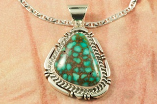 "Genuine High Grade Kingman Web Turquoise set in Sterling Silver Pendant. Created by Navajo Artist Freddy Charley. Signed by the artist. The Mineral Park Mine, in the Cerbat Mountains 14 miles northwest of Kingman, was first mined by Indians centuries before white man came to the area. It is one of the three sites of prehistoric mining localities in the state of Arizona. Mineral Park was the most extensively worked area by the Indians of the three. S.A. ""Chuck"" Colbaugh found a cache of stone hammers uncovered in ancient trenches and tunnels, when he had the turquoise mining concession in May of 1962. Ithaca Peak and Turquoise Mine (formally called Aztec Mountain or Aztec Peak) are the most famous of the peaks in the area containing turquoise. Free 18"" Sterling Silver Chain with purchase of pendant."