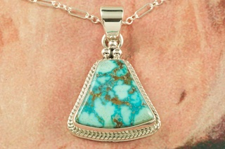 "Genuine High Grade Kingman Web Turquoise set in Sterling Silver Pendant. Created by Navajo Artist Lucy Valencia. Signed L. J. by the artist. The Mineral Park Mine, in the Cerbat Mountains 14 miles northwest of Kingman, was first mined by Indians centuries before white man came to the area. It is one of the three sites of prehistoric mining localities in the state of Arizona. Mineral Park was the most extensively worked area by the Indians of the three. S.A. ""Chuck"" Colbaugh found a cache of stone hammers uncovered in ancient trenches and tunnels, when he had the turquoise mining concession in May of 1962. Ithaca Peak and Turquoise Mine (formally called Aztec Mountain or Aztec Peak) are the most famous of the peaks in the area containing turquoise. Free 18"" Sterling Silver Chain with purchase of pendant."