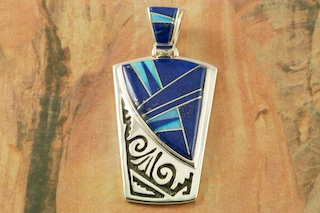 "Sunning Pendant featuring Genuine Blue Lapis inlaid between ribbons of Sterling Silver with Fire and Ice Lab Opal Accents. Free 18"" Sterling Silver Chain with Purchase of Pendant. Designed by Navajo Artist Calvin Begay. Signed by the artist."