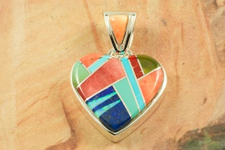 "Beautiful Heart Pendant featuring Genuine Turquoise, Spiny Oyster Shell, Gaspeite and Blue Lapis inlaid between ribbons of Sterling Silver. Free 18"" Sterling Silver Chain with Purchase of Pendant. Designed by Navajo Artist Calvin Begay. Signed by the artist."