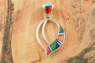 "Stunning Pendant featuring Genuine Turquoise, Spiny Oyster Shell and Blue Lapis inlaid between ribbons of Sterling Silver. Free 18"" Sterling Silver Chain with Purchase of Pendant. Designed by Navajo Artist Calvin Begay. Signed by the artist."
