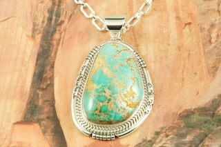 "Stunning Pendant featuring Genuine Pilot Mountain Turquoise set in Sterling Silver. Free 18 inch Sterling Silver Chain with purchase of pendant. The Pilot Mountain Mine is located in western Nevada, east of the small town of Mina. Pilot Mountain turquoise forms in hard veins with color ranging from bright blue to dark blue with a greenish cast. Dark brown limonite mottled patterns are associated with this material. Most Pilot Mountain turquoise is called ""grass roots"", meaning the best deposits are found within ten feet of the surface. Created by Navajo Artist Sampson Jake. Signed by the artist."