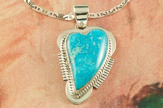 "Genuine High Grade Kingman Turquoise set in Sterling Silver Pendant. Created by Navajo Artist Sampson Jake. Signed by the artist. The Mineral Park Mine, in the Cerbat Mountains 14 miles northwest of Kingman, was first mined by Indians centuries before white man came to the area. It is one of the three sites of prehistoric mining localities in the state of Arizona. Mineral Park was the most extensively worked area by the Indians of the three. S.A. ""Chuck"" Colbaugh found a cache of stone hammers uncovered in ancient trenches and tunnels, when he had the turquoise mining concession in May of 1962. Ithaca Peak and Turquoise Mine (formally called Aztec Mountain or Aztec Peak) are the most famous of the peaks in the area containing turquoise. Free 18"" Sterling Silver Chain with purchase of pendant."