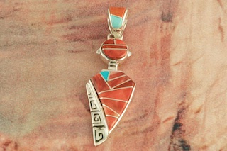 "Sterling Silver Kachina Pendant featuring  Genuine Fire Spiny Oyster Shell with accents of Turquoise inlaid between ribbons of Sterling Silver. Free 18"" Sterling Silver Chain with Purchase of Pendant. Designed by Navajo Artist Calvin Begay. Signed by the artist."