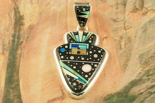 "Stunning Night Sky Arrowhead Pendant featuring Genuine Black Jade with accents of Sleeping Beauty Turquoise, Picture Jasper, Mother of Pearl and Red Coral inlaid in Sterling Silver. Beautiful Fire and Ice Lab Opal Accents. The reverse side features a Contemporary Sterling Silver Design. Free 18"" Sterling Silver Chain with Purchase of Pendant. Designed by Navajo Artist Calvin Begay. Signed by the artist."