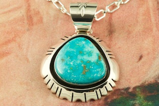 "Stunning Pendant featuring Genuine High Grade Kingman Turquoise set in Sterling Silver. Created by Navajo Artist Freddy Charley. Signed by the artist. The Mineral Park Mine, in the Cerbat Mountains 14 miles northwest of Kingman, was first mined by Indians centuries before white man came to the area. It is one of the three sites of prehistoric mining localities in the state of Arizona. Mineral Park was the most extensively worked area by the Indians of the three. S.A. ""Chuck"" Colbaugh found a cache of stone hammers uncovered in ancient trenches and tunnels, when he had the turquoise mining concession in May of 1962. Ithaca Peak and Turquoise Mine (formally called Aztec Mountain or Aztec Peak) are the most famous of the peaks in the area containing turquoise. Free 18"" Sterling Silver Chain with purchase of pendant."
