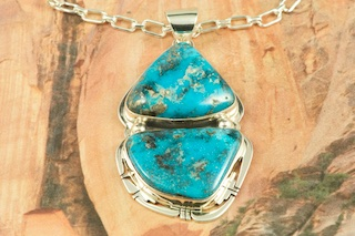 "Genuine Apache Blue Turquoise set in Sterling Silver Pendant. Free 18"" Sterling Silver Chain with purchase. Created by Navajo Artist Phillip Sanchez. Signed by the artist. The Apache Blue Mine turquoise mine, is a small mine with lots of potential. The mine is located near Tonopah, Nevada in the Candelaria Mountain range. In recent years the mine, (an open pit) has re-opened rendering Apache Blue turquoise with beautiful blue stones with eye popping black matrix. This high quality Apache turquoise is very rare and hard to find, even in this mine, but it's what every turquoise miner is searching for. Unfortunately only a small amount of this nice natural hard turquoise with really beautiful dark blue, webbed nuggets have been discovered. This turquoise is truly some of the nicest from Nevada."