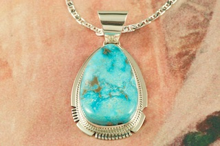 "Genuine High Grade Kingman Turquoise set in Sterling Silver Pendant. Created by Navajo Artist Larson Lee. Signed by the artist. The Mineral Park Mine, in the Cerbat Mountains 14 miles northwest of Kingman, was first mined by Indians centuries before white man came to the area. It is one of the three sites of prehistoric mining localities in the state of Arizona. Mineral Park was the most extensively worked area by the Indians of the three. S.A. ""Chuck"" Colbaugh found a cache of stone hammers uncovered in ancient trenches and tunnels, when he had the turquoise mining concession in May of 1962. Ithaca Peak and Turquoise Mine (formally called Aztec Mountain or Aztec Peak) are the most famous of the peaks in the area containing turquoise. Free 18"" Sterling Silver Chain with purchase of pendant."