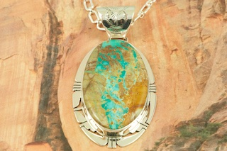 "Mother Nature is Amazing! The beautiful pattern in the stone (called the matrix) is all natural. Genuine Boulder Turquoise set in Sterling Silver Pendant. Free 18"" Sterling Silver Chain with purchase. Created by Navajo Artist Phillip Sanchez. Signed by the artist. The cabachon is Boulder Turquoise,you can see the veins of Turquoise running through the host rock. The Boulder Turquoise Mine is located in northeast Nevada. It was discovered in 1970 by a Shoshone sheep herder. Production is small due to the remote location and winter weather. Boulder Turquoise is valued for both it's beauty and rarity. Every stone is unique."
