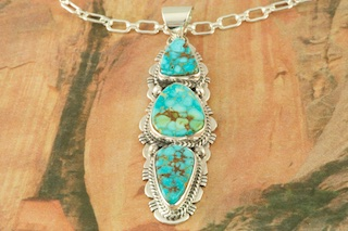 "Genuine Turquoise Mountain Mine Stones set in Sterling Silver Pendant. Free 18"" Sterling Silver Chain with Purchase of Pendant. Created by Navajo Artist Sampson Jake. Signed by the artist. The Turquoise Mountain Mine is located in the Mineral Park Mining District, Mohave County, Arizona. Although Turquoise Mountain is located near the Kingman Turquoise Mine it is considered a classic mine in its own right because the Turquoise is so different in appearance. It is also known as ""Old Man Turquoise""."