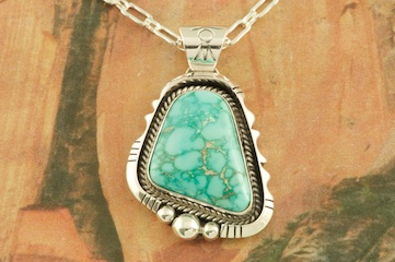 "Genuine High Grade Kingman Turquoise set in Sterling Silver Pendant. Created by Navajo Artist Joe Piaso. Signed by the artist. The Mineral Park Mine, in the Cerbat Mountains 14 miles northwest of Kingman, was first mined by Indians centuries before white man came to the area. It is one of the three sites of prehistoric mining localities in the state of Arizona. Mineral Park was the most extensively worked area by the Indians of the three. S.A. ""Chuck"" Colbaugh found a cache of stone hammers uncovered in ancient trenches and tunnels, when he had the turquoise mining concession in May of 1962. Ithaca Peak and Turquoise Mine (formally called Aztec Mountain or Aztec Peak) are the most famous of the peaks in the area containing turquoise. Free 18"" Sterling Silver Chain with purchase of pendant."