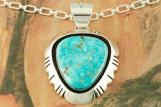 "Genuine Turquoise Mountain Nugget set in Sterling Silver Pendant. Free 18"" Sterling Silver Chain with Purchase of Pendant. Created by Navajo Artist Freddy Charley. Signed by the artist. The Turquoise Mountain Mine is located in the Mineral Park Mining District, Mohave County, Arizona. Although Turquoise Mountain is located near the Kingman Turquoise Mine it is considered a classic mine in its own right because the Turquoise is so different in appearance. It is also known as ""Old Man Turquoise""."