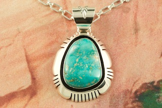 "Genuine High Grade Kingman Turquoise set in Sterling Silver Pendant. Created by Navajo Artist Freddy Charley. Signed by the artist. The Mineral Park Mine, in the Cerbat Mountains 14 miles northwest of Kingman, was first mined by Indians centuries before white man came to the area. It is one of the three sites of prehistoric mining localities in the state of Arizona. Mineral Park was the most extensively worked area by the Indians of the three. S.A. ""Chuck"" Colbaugh found a cache of stone hammers uncovered in ancient trenches and tunnels, when he had the turquoise mining concession in May of 1962. Ithaca Peak and Turquoise Mine (formally called Aztec Mountain or Aztec Peak) are the most famous of the peaks in the area containing turquoise. Free 18"" Sterling Silver Chain with purchase of pendant."