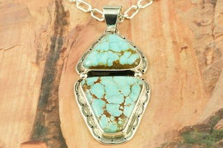 "Genuine Number 8 Mine Turquoise Stone set in Sterling Silver Pendant. Free 18"" Sterling Silver Chain with Purchase of Pendant. Created by Navajo Artist Arkie Nelson. Signed by the artist. The Number 8 mine is located in Eureka County Nevada. Since 1976 there has been no Number 8 Turquoise mined. There is however, an existing stock pile that Mr. Dowell Ward, the last owner of the Number 8 mine, had stocked away for later sorting. The Turquoise is a collector's item--because once the reserve is gone there will be no more material released onto the market. The Gold Mining Company owns the claim to the Number 8 mine and it has been swallowed up by the gold mining operations. This is some of the last Number 8 Turquoise to be had and will be a great addition to your collection."