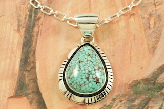 "Genuine High Grade Kingman Turquoise set in Sterling Silver Pendant. Created by Navajo Artist Jimmy Secatero. Signed by the artist. The Mineral Park Mine, in the Cerbat Mountains 14 miles northwest of Kingman, was first mined by Indians centuries before white man came to the area. It is one of the three sites of prehistoric mining localities in the state of Arizona. Mineral Park was the most extensively worked area by the Indians of the three. S.A. ""Chuck"" Colbaugh found a cache of stone hammers uncovered in ancient trenches and tunnels, when he had the turquoise mining concession in May of 1962. Ithaca Peak and Turquoise Mine (formally called Aztec Mountain or Aztec Peak) are the most famous of the peaks in the area containing turquoise. Free 18"" Sterling Silver Chain with purchase of pendant."