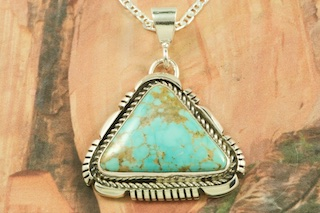 "Genuine Number 8 Mine Turquoise Stone set in Sterling Silver Pendant. Free 18"" Sterling Silver Chain with Purchase of Pendant. Created by Navajo Artist Edison Gruber. Signed by the artist. The Number 8 mine is located in Eureka County Nevada. Since 1976 there has been no Number 8 Turquoise mined. There is however, an existing stock pile that Mr. Dowell Ward, the last owner of the Number 8 mine, had stocked away for later sorting. The Turquoise is a collector's item--because once the reserve is gone there will be no more material released onto the market. The Gold Mining Company owns the claim to the Number 8 mine and it has been swallowed up by the gold mining operations. This is some of the last Number 8 Turquoise to be had and will be a great addition to your collection."