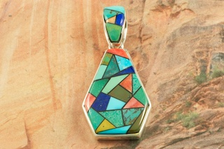 "A Beautiful Mosaic of Genuine Turquoise, Spiny Oyster Shell, Blue Lapis and Black Jade inlaid in Sterling Silver. Reversible Pendant features a Sterling Silver Contemporary Design. Free 18"" Sterling Silver Chain with Purchase of Pendant. Stunning Pendant Designed by Navajo Artist Calvin Begay. Signed by the artist."