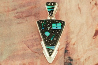"This Arrowhead Pendant is a work of art! Stunning Starry Night Design featuring Genuine Acoma Jet inlaid in Sterling Silver with Beautiful Fire and Ice Lab Opal Moon and Shooting Star! Free 18"" Sterling Silver Chain with Purchase of Pendant. Designed by Navajo Artist Calvin Begay. Signed by the artist."