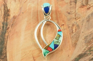 "Stunning Pendant featuring a Mosaic of Genuine Turquoise, Spiny Oyster Shell, Gaspeite and Blue Lapis inlaid in Sterling Silver. Free 18"" Sterling Silver Chain with Purchase of Pendant. Designed by Navajo Artist Calvin Begay. Signed by the artist."