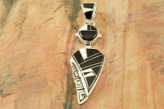 "Sunning Pendant featuring Genuine Black Acoma Jet and White Agate inlaid between ribbons of Sterling Silver. Free 18"" Sterling Silver Chain with Purchase of Pendant. Designed by Navajo Artist Calvin Begay. Signed by the artist."