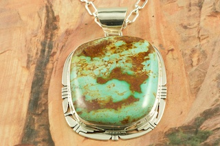 "Stunning Pendant featuring Genuine Pilot Mountain Turquoise set in Sterling Silver. Free 18 inch Sterling Silver Chain with purchase of pendant. The Pilot Mountain Mine is located in western Nevada, east of the small town of Mina. Pilot Mountain turquoise forms in hard veins with color ranging from bright blue to dark blue with a greenish cast. Dark brown limonite mottled patterns are associated with this material. Most Pilot Mountain turquoise is called ""grass roots"", meaning the best deposits are found within ten feet of the surface. Created by Navajo Artist Phillip Sanchez. Signed by the artist."