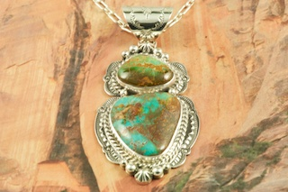 "Stunning Pendant featuring Genuine Pilot Mountain Turquoise set in Sterling Silver. Free 18 inch Sterling Silver Chain with purchase of pendant. The Pilot Mountain Mine is located in western Nevada, east of the small town of Mina. Pilot Mountain turquoise forms in hard veins with color ranging from bright blue to dark blue with a greenish cast. Dark brown limonite mottled patterns are associated with this material. Most Pilot Mountain turquoise is called ""grass roots"", meaning the best deposits are found within ten feet of the surface. Created by Navajo Artist Freddy Charley. Signed by the artist."