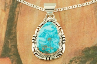 "Genuine Kingman Turquoise set in Sterling Silver Pendant. Created by Navajo Artist John Nelson. Signed by the artist. The Mineral Park Mine, in the Cerbat Mountains 14 miles northwest of Kingman, was first mined by Indians centuries before white man came to the area. It is one of the three sites of prehistoric mining localities in the state of Arizona. Mineral Park was the most extensively worked area by the Indians of the three. S.A. ""Chuck"" Colbaugh found a cache of stone hammers uncovered in ancient trenches and tunnels, when he had the turquoise mining concession in May of 1962. Ithaca Peak and Turquoise Mine (formally called Aztec Mountain or Aztec Peak) are the most famous of the peaks in the area containing turquoise. Free 18"" Sterling Silver Chain with purchase of pendant."